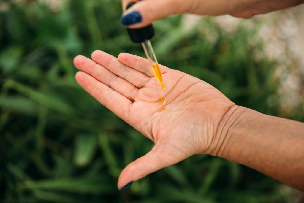 Photo of a lady dropping a drop of DH Aromatology Serum in her hand.